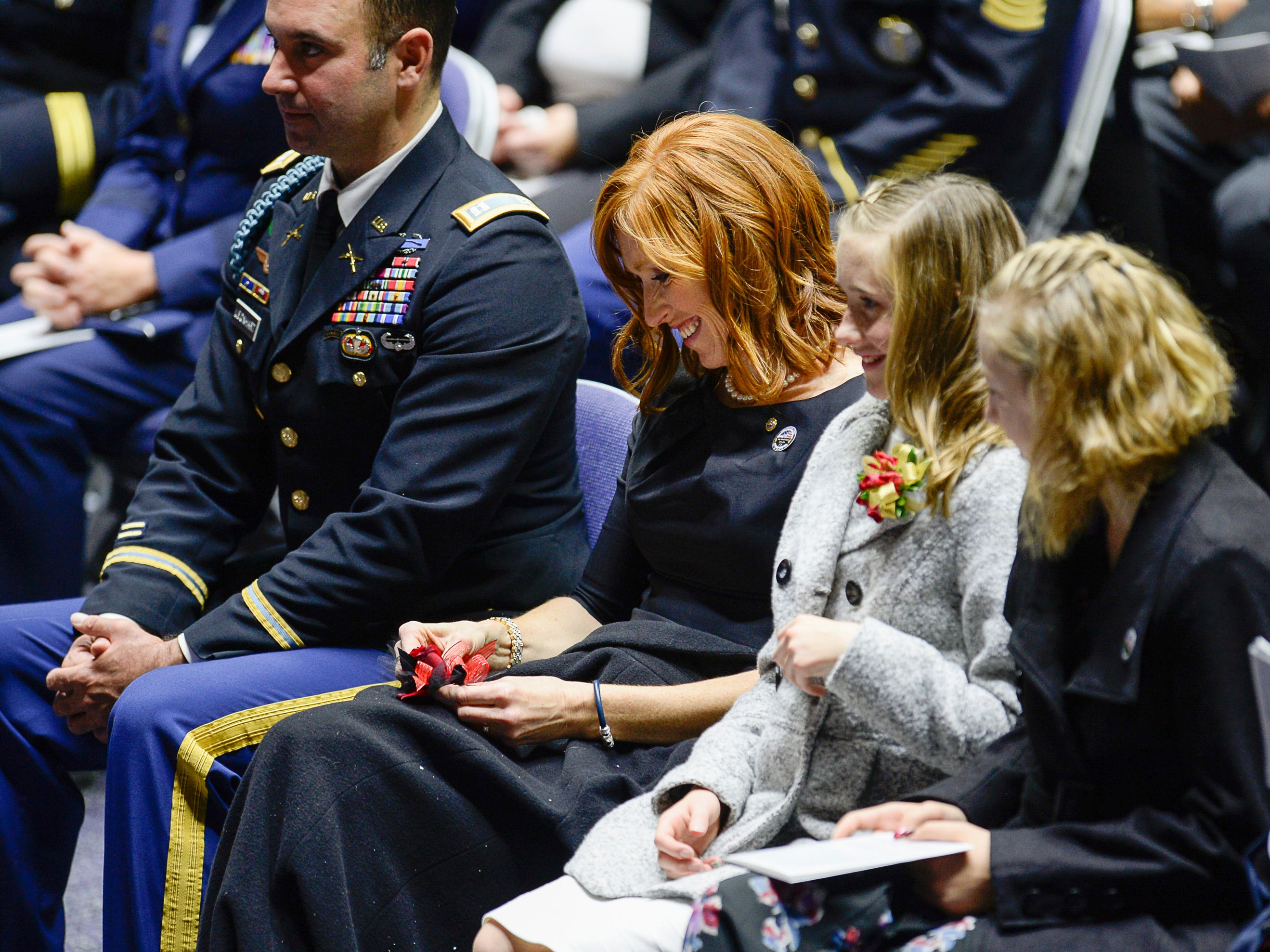 Jennie Taylor laughs alongside his children as funny stories are relayed about her husband Maj. Brent R. Taylor during his funeral services at Weber State University's Dee Event Center in Ogden, Utah on Saturday, Nov. 17, 2018.