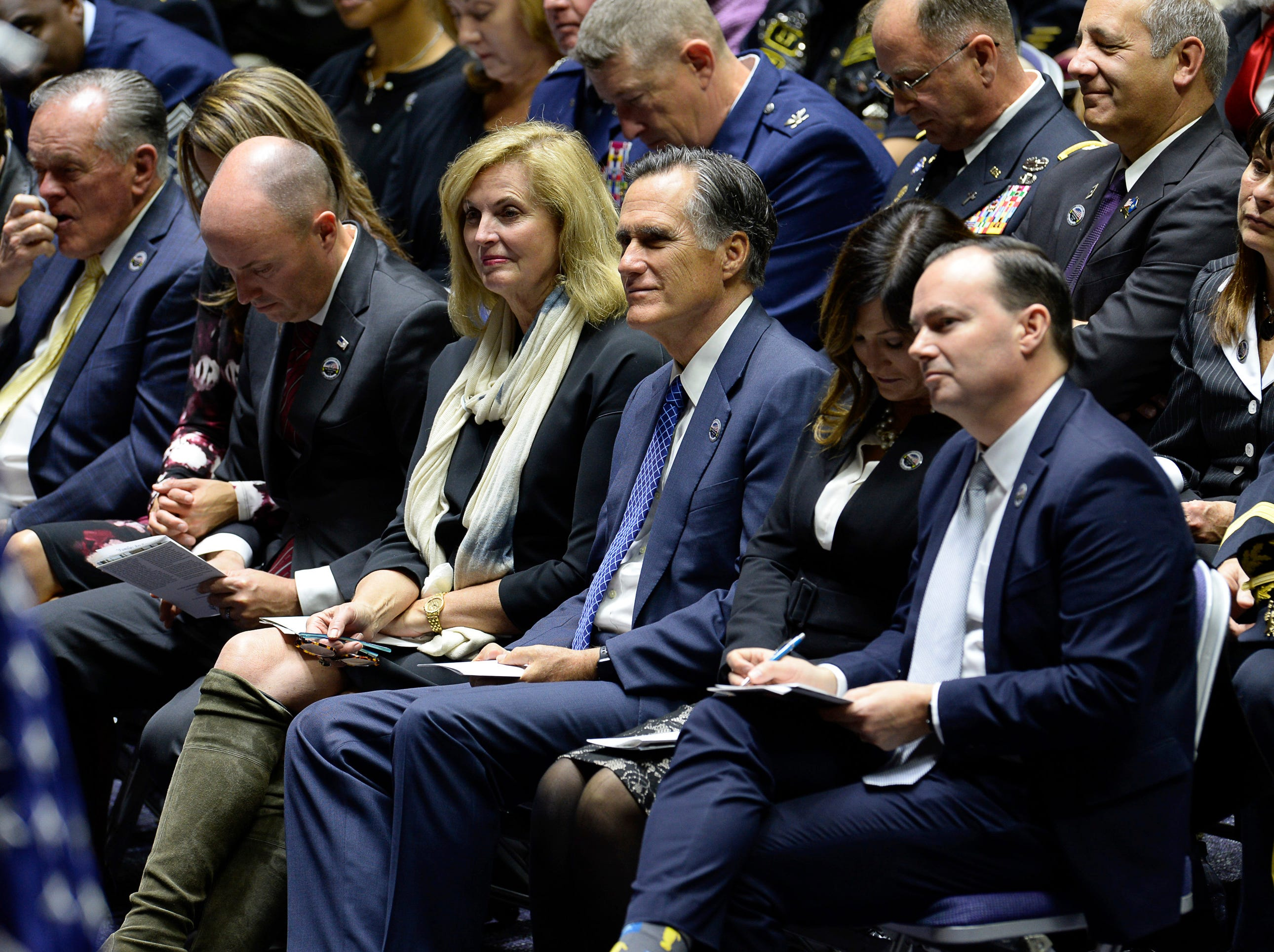 Sen.-elect Mitt Romney, center, attends funeral services for Maj. Brent R. Taylor, alongside Sen. Mike Lee and Lt. Gov. Spencer Cox at Weber State University's Dee Event Center in Ogden, Utah on Saturday, Nov. 17, 2018.