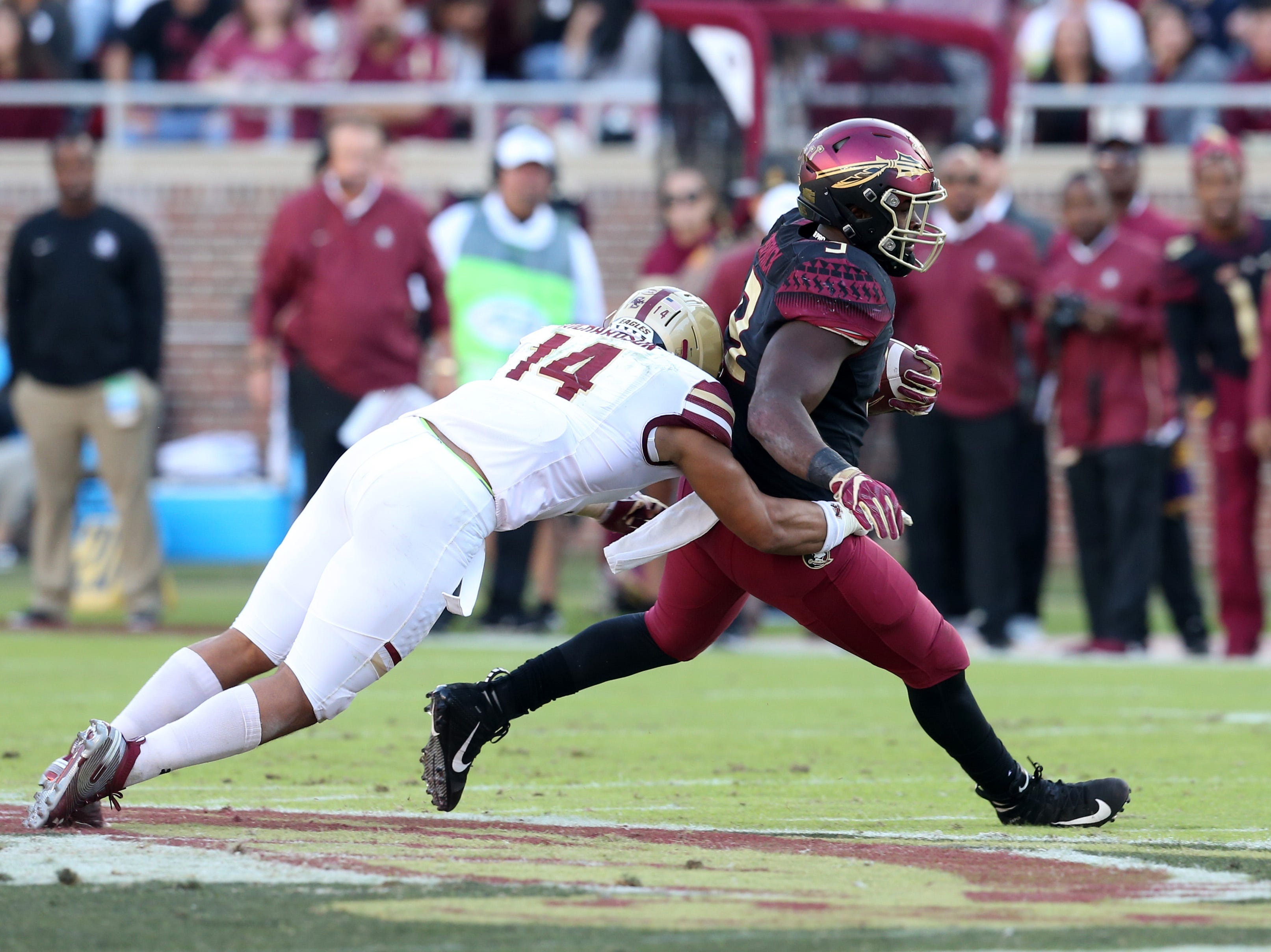 Florida State Seminoles running back Jacques Patrick (9) tries to get every yard possible before Boston College Eagles linebacker Max Richardson (14) takes him down as the Florida State Seminoles face off against the Boston College Eagles at Doak S. Campbell Stadium, Saturday, Nov. 17, 2018.