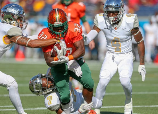 FAMU running back DeShawn Smith runs over a defender in the Florida Classic.