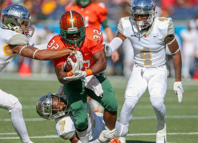 FAMU running back DeShawn Smith runs over a Bethune-Cookman defender in the 2018 Florida Classic.