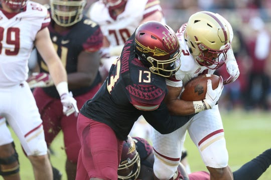 Florida State Seminoles defensive end Joshua Kaindoh (13) tackles Boston College Eagles running back AJ Dillon (2) as the Florida State Seminoles face off against the Boston College Eagles at Doak S. Campbell Stadium, Saturday, Nov. 17, 2018.