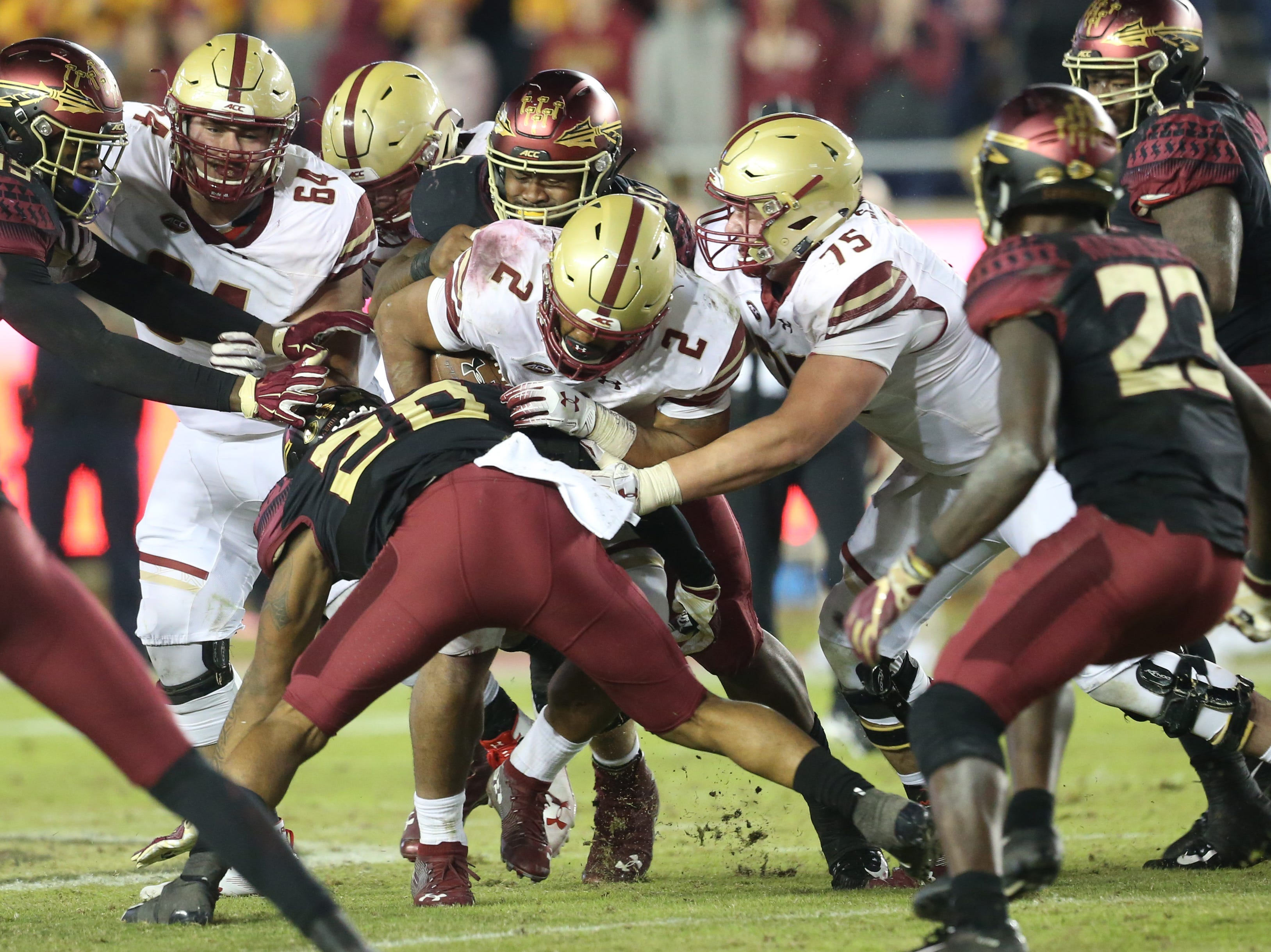Florida State Seminoles defensive back Jaiden Woodbey (20) latches onto Boston College Eagles running back AJ Dillon (2) as the Florida State Seminoles face off against the Boston College Eagles at Doak S. Campbell Stadium, Saturday, Nov. 17, 2018.
