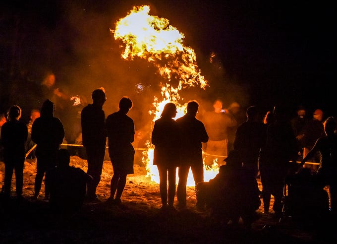 Festival goers gather around a bonfire as it lights up the night Saturday, Nov. 17, 2018, during the Beachside Bonfire Fest in front of Mulligan's Beach House Bar & Grill on Sexton Plaza Beach in Vero Beach. The event, a part of Vero Beach's Centennial Celebration, featured four different themed bonfires along the beach with food, drinks, and live music.
