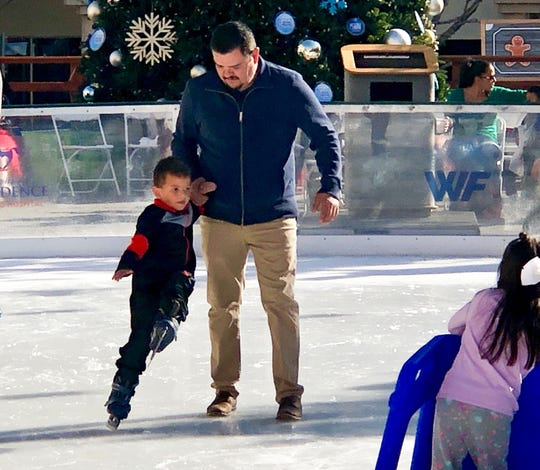 Oscar Rascon leads his son, Daniel Rascon, 5, on the ice Sunday in Downtown El Paso. The Celebration of Lights Parade and tree lighting ceremony officially kicked off WinterFest 2018.