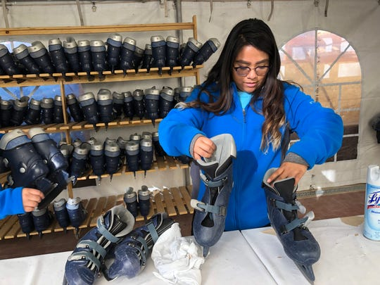Erika Aguilar checks out ice skates at the ice rink at Arts Festival Plaza in Downtown.