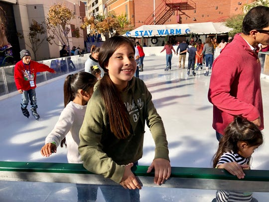 Meliza Baez, 11, of El Paso, tries ice skating for the first time Sunday at the seasonal ice rink at Downtown Arts Festival Plaza during Winterfest 2018.