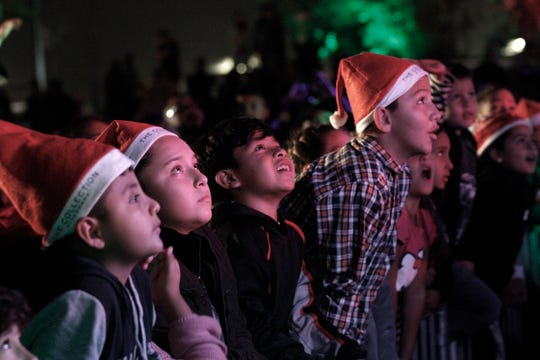 Children watch the live entertainment, from the front of the stage during the annual Christmas Tree Lighting celebration Saturday at The Collection at RiverPark.