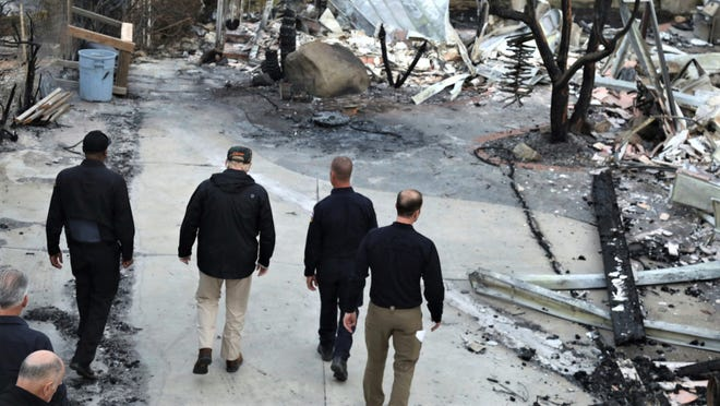 President Donald Trump, second from left, tours the Woolsey Fire ravaged neighborhood on Dume Drive in Malibu on Saturday, joined by first responders and officials.