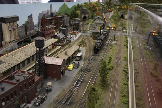 A model train goes through a working signal, the same kind that would be found on real train tracks.
