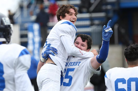 Dobbs Ferry's Thomas Ritch (21) and Michael McGoey (65) celebrate Dobbs Ferry's 55-22 victory over Ogdensburg to win the state Class C semifinal game at Middletown High School Nov. 17, 2018.