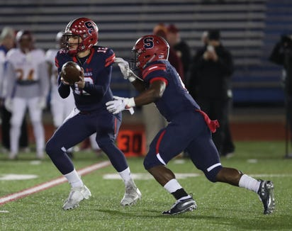 Stepinac's Joey Carino (12) hands off to Malik Grant (4) during their 29-18 win over Cardinal Hayes in the CHSFL Class 'AA' Championship Game at Mitchel Field Complex in Uniondale on Saturday, November 17, 2018.