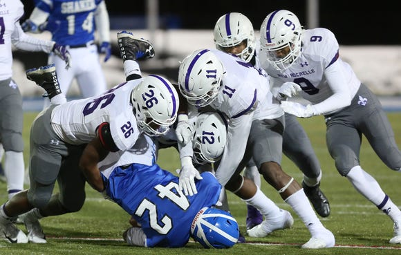 New Rochelle defenders combine to stop Shaker's Mike Amponsah (42) on a first half run during the state Class AA semifinal game at Middletown High School Nov. 17, 2018.