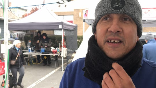 """Bill Batson talks about his new """"Nyack Sketch Log, Vol. 2,"""" which includes 55 drawings and stories, six of them drawn from the weekly Nyack Farmers' Market, where Batson is official artist-in-residence. The new sketch log will be launched at a party at 6 p.m., Nov. 27 at Nyack's Hudson House. Behind Batson is Scott Jennings, of X-Calibur Knife & Scissor Sharpening, one of the artisans featured in the new book."""