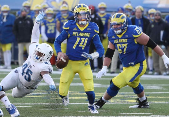 Delaware quarterback Nolan Henderson avoids Villanova's Lorenzo Hernandez as teammate Connor Lutz moves to protect him in the fourth quarter of the Blue Hens' 42-21 loss at Delaware Stadium Saturday.