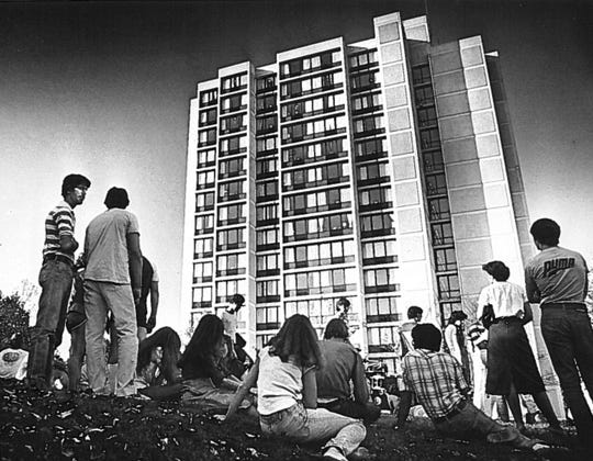 Students stand outside The Christiana Towers in 1979 after a fire alarm forces them to evacuate the building. The University of Delaware closed both 17-story Christiana Towers residence halls last year.