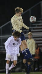 Appoquinimink's Cody Niggebrugge (in white) battles for possession last fall against Salesianum's Ben Strine.