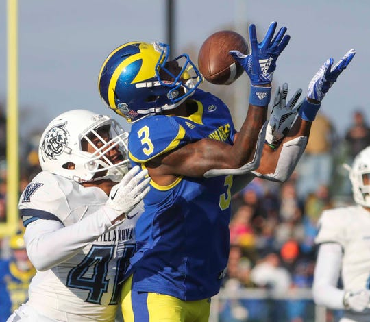 Delaware receiver Joe Walker is interfered with by Villanova 's Christian Benford, preventing a long catch but causing a penalty in the third quarter of the Blue Hens' 42-21 loss at Delaware Stadium Saturday.