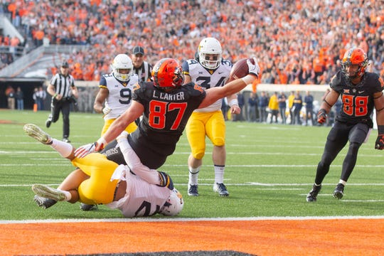 Oklahoma State's Logan Carter scores a touchdown in a 2018 game against West Virginia.