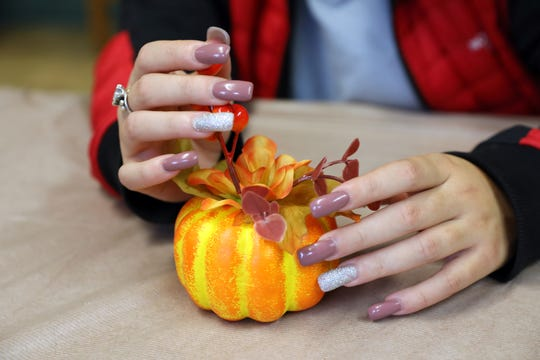 A young woman plays with a Thanksgiving decoration while talking about her time at the Avondale Youth Center.