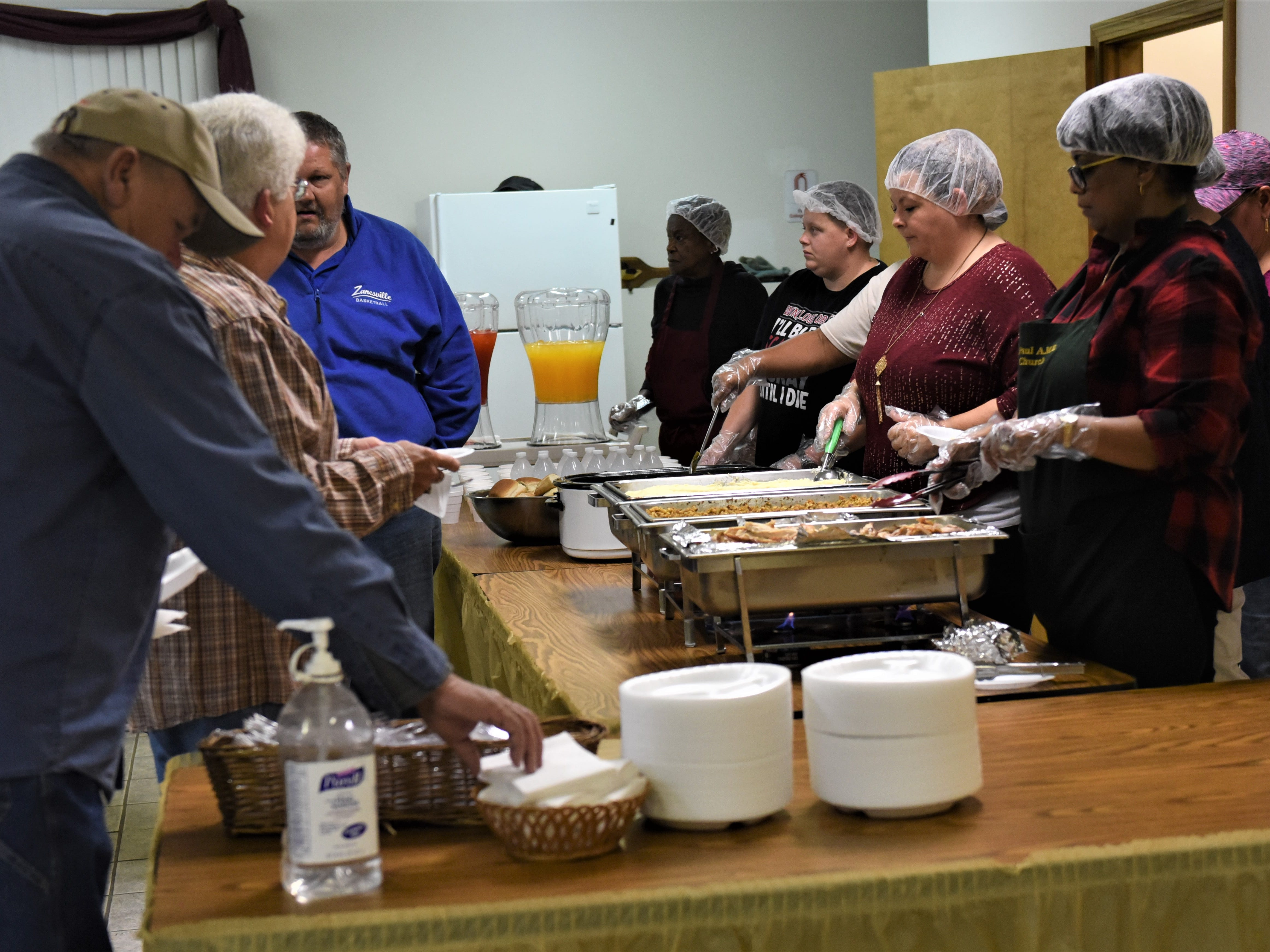 Servers prepare to dish out food during Saturday's Thanksgiving meal at St. Paul AME Church on Pine Street in Zanesville.