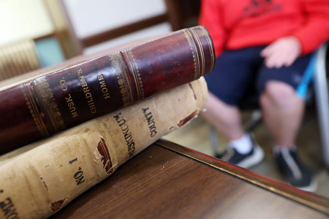 A young man talks about his time at the Avondale Youth Center near a book of records dating back to the earliest days when it was a children's home.