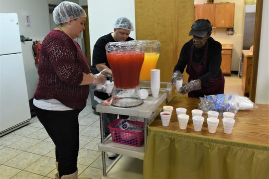 Casie Sammons (left), Jo Williams (center) and Saundra Edwards (right) set out drinks for Saturday's Thanksgiving meal at St. Paul AME Church on Pine Street in Zanesville.