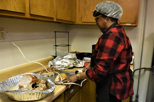 Veronica Barnett cuts the turkey in preparation for Saturday's Thanksgiving meal at St. Paul AME Church on Pine Street in Zanesville.
