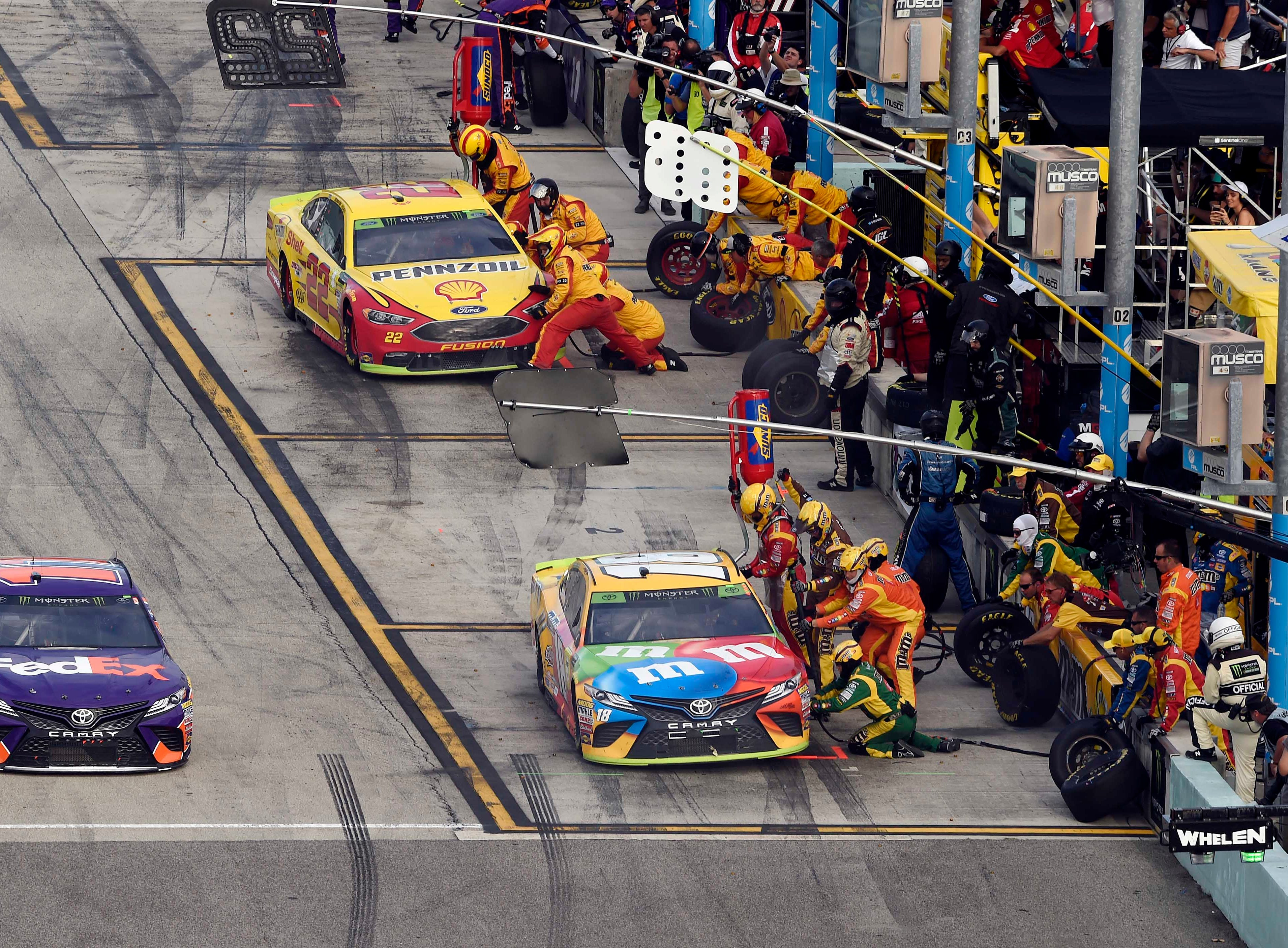 As the pit crews of Kyle Busch (18) and Joey Logano (22) work on their cars, Denny Hamlin speeds past during the the Ford EcoBoost 400 at Homestead-Miami Speedway.