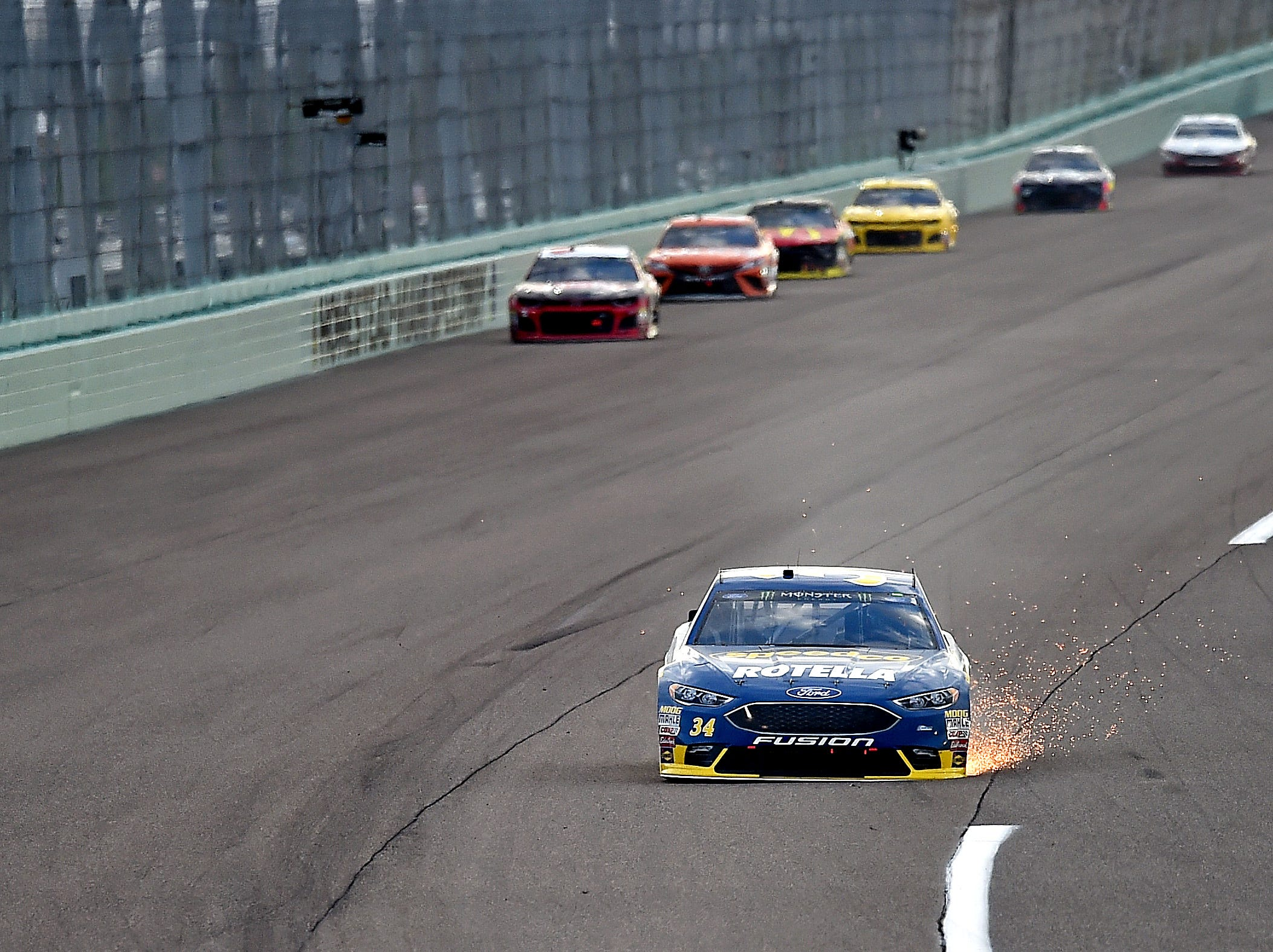 Michael McDowell (34) throws sparks from his car during the Ford EcoBoost 400 at Homestead-Miami Speedway.
