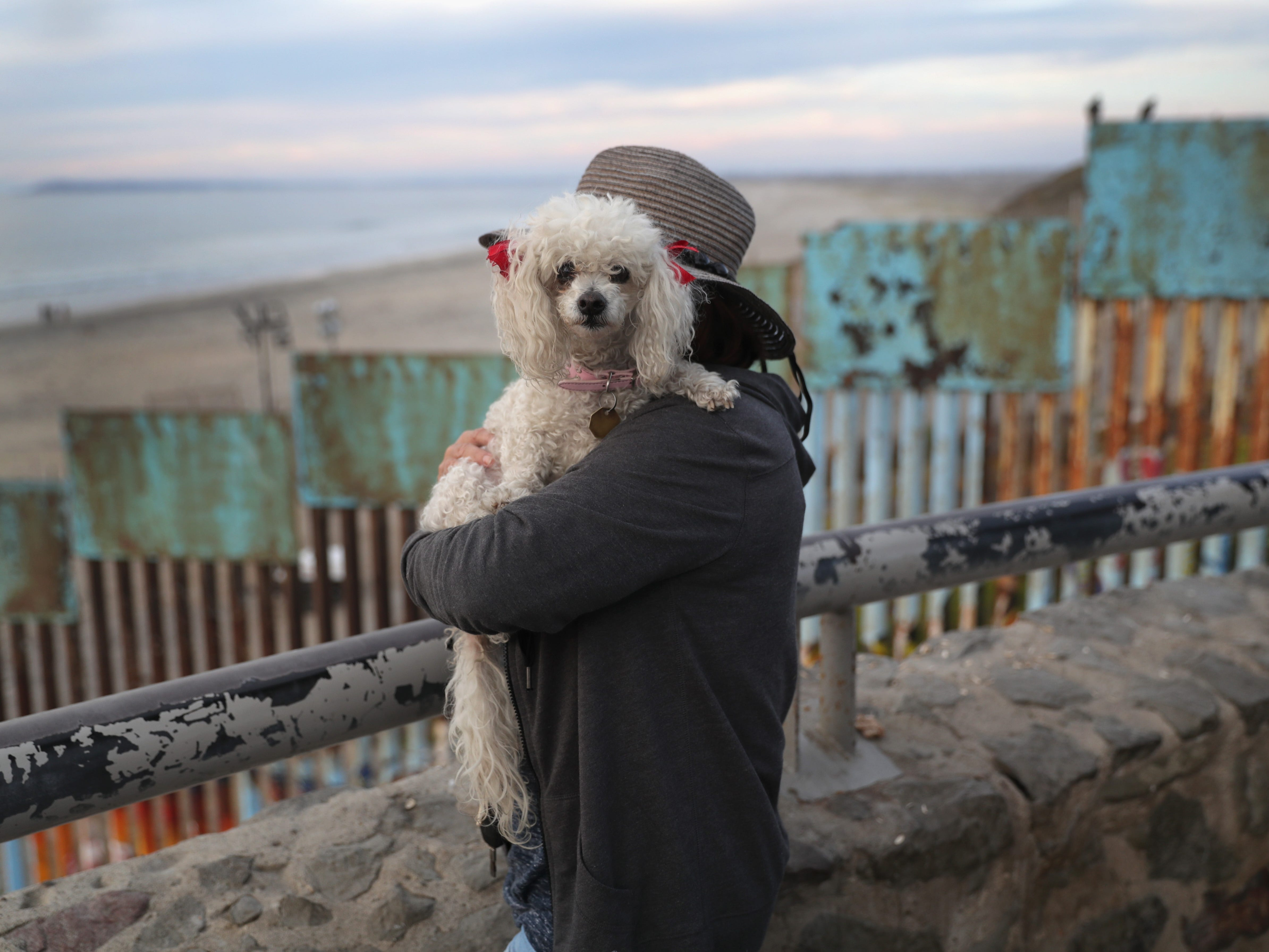 Playas de Tijuana resident Juantia Leon holds her poodle Mini while taking in the view of the Pacific Ocean next to the U.S.-Mexico border fence on Nov. 17, 2018, in Tijuana, Mexico.