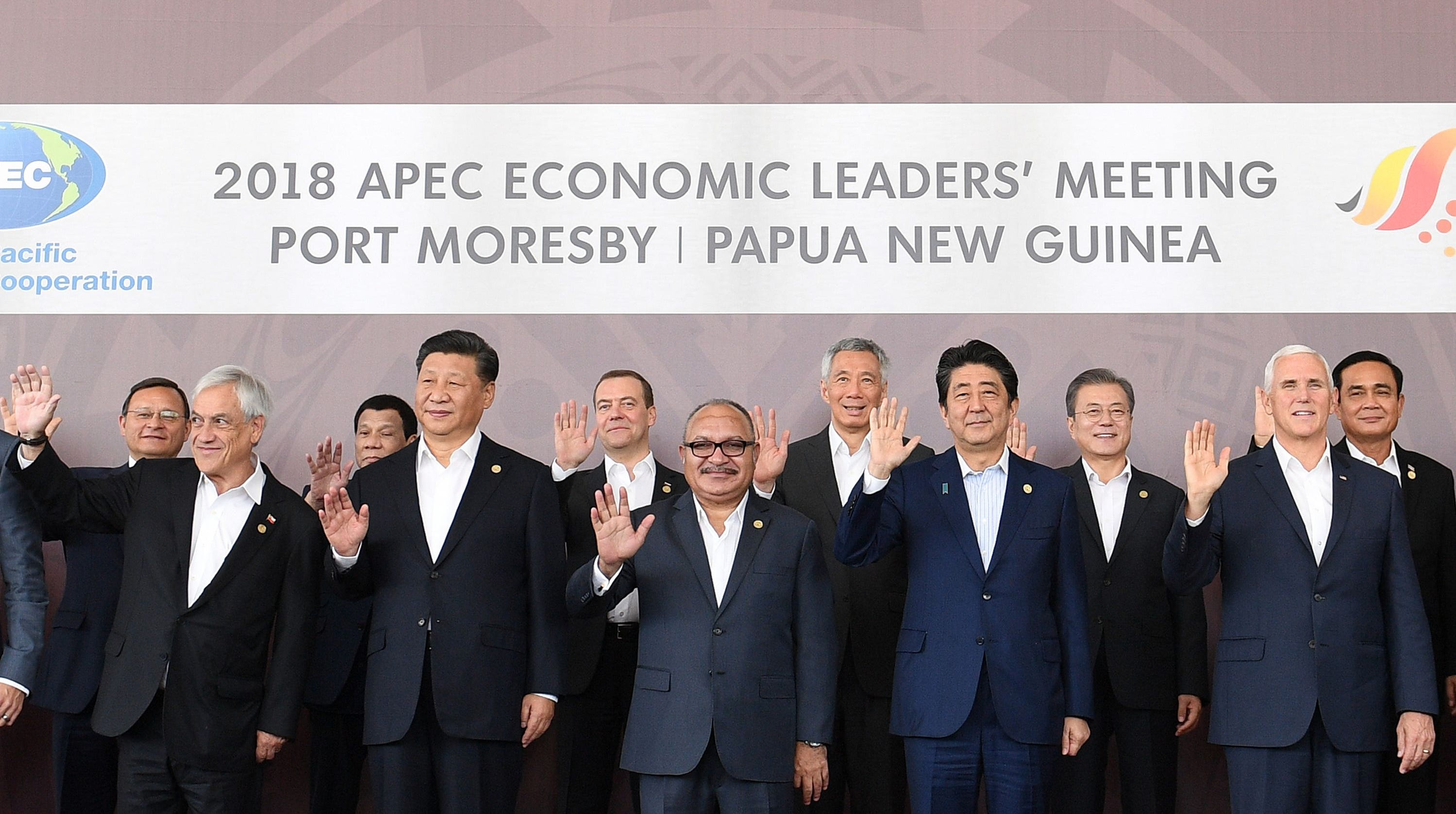 """Chile's President Sebastian Pinera, China's President Xi Jinping, Papua New Guinea's Prime Minister Peter O'Neill, Japan's Prime Minister Shinzo Abe and US Vice President Mike Pence wave with (back row L to R) Peru's Foreign Minister Nestor Popolizio, Philippine President Rodrigo Duterte, Russia's Prime Minister Dmitry Medvedev, Singapore's Prime Minister Lee Hsien Loong, South Korea's President Moon Jae-in and Thailand's Prime Minister Prayut Chan-O-Cha as they pose for a """"family photo"""" during the Asia-Pacific Economic Cooperation (APEC) Summit in Port Moresby on November 18, 2018."""