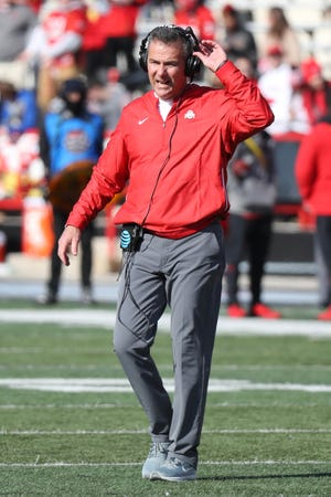 Ohio State Buckeyes head coach Urban Meyer walks onto the field to check the status of an injured player against the Maryland Terrapins at Capital One Field at Maryland Stadium.