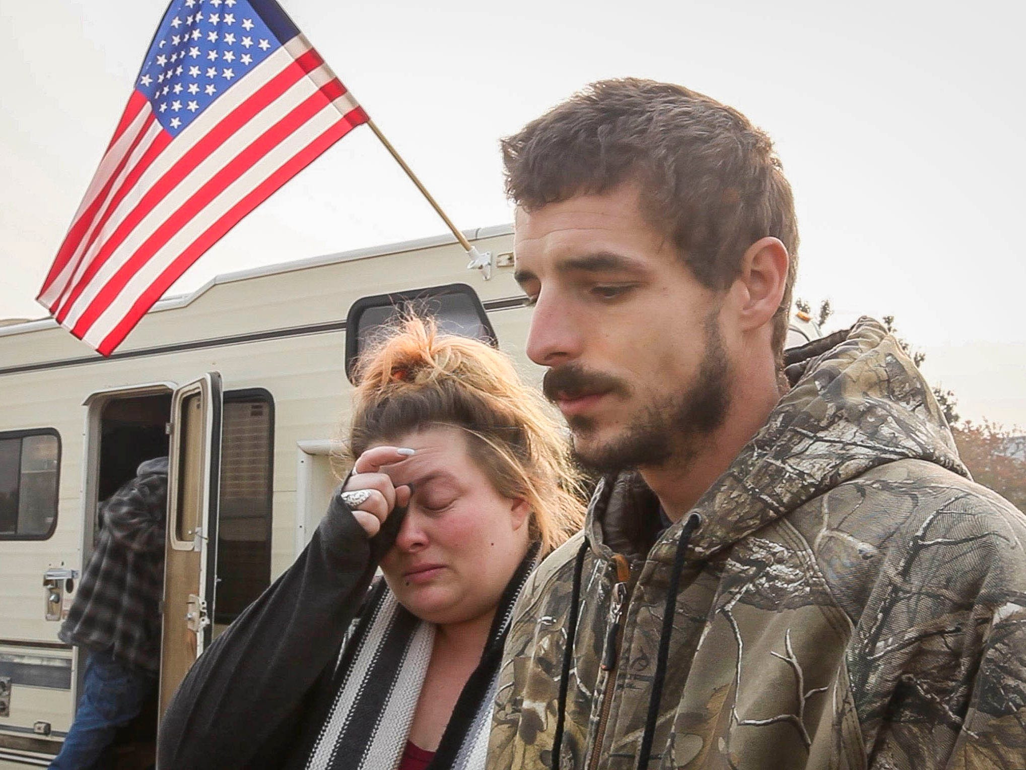 Ryan Belcher, left, and his wife Casey sit next to a pick-up truck that Ryan's boss loaned them. The Belcher family lost their home and vehicles in the Camp Fire. The children sleep in the truck at night and the parents share a small tent in a field next to the Walmart in Chico, Calif., Nov. 17, 2018.