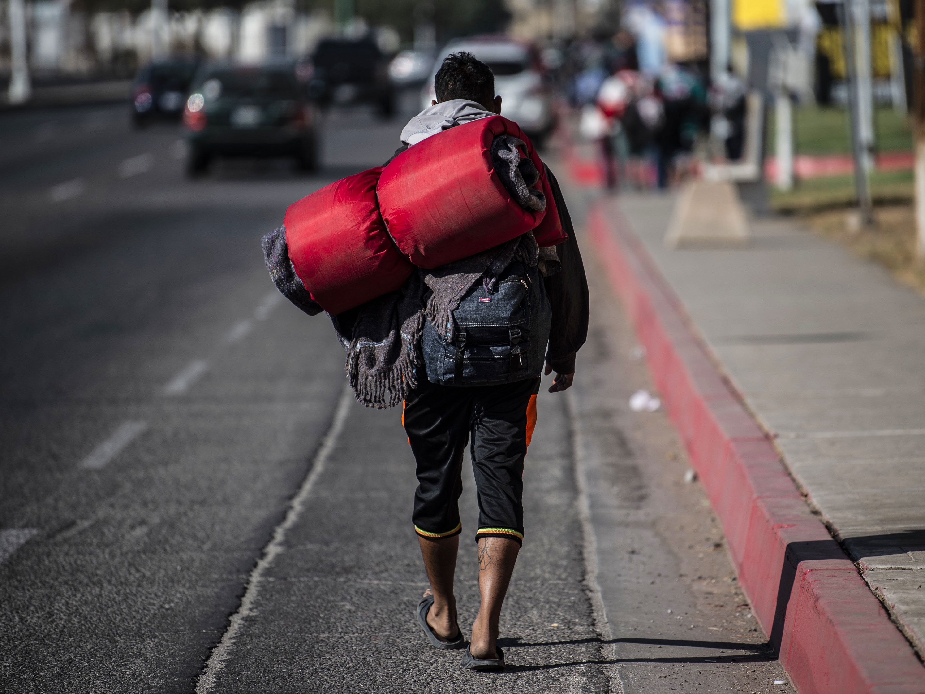 "A Central American migrant walks towards the United States, through Mexicali, Mexico, on Nov. 18, 2018. The Central American migrant caravan faced a desperate situation Friday as its numbers swelled at the US-Mexican border, where it got a cold welcome and a warning that its chances of entering the United States were ""almost nil."""