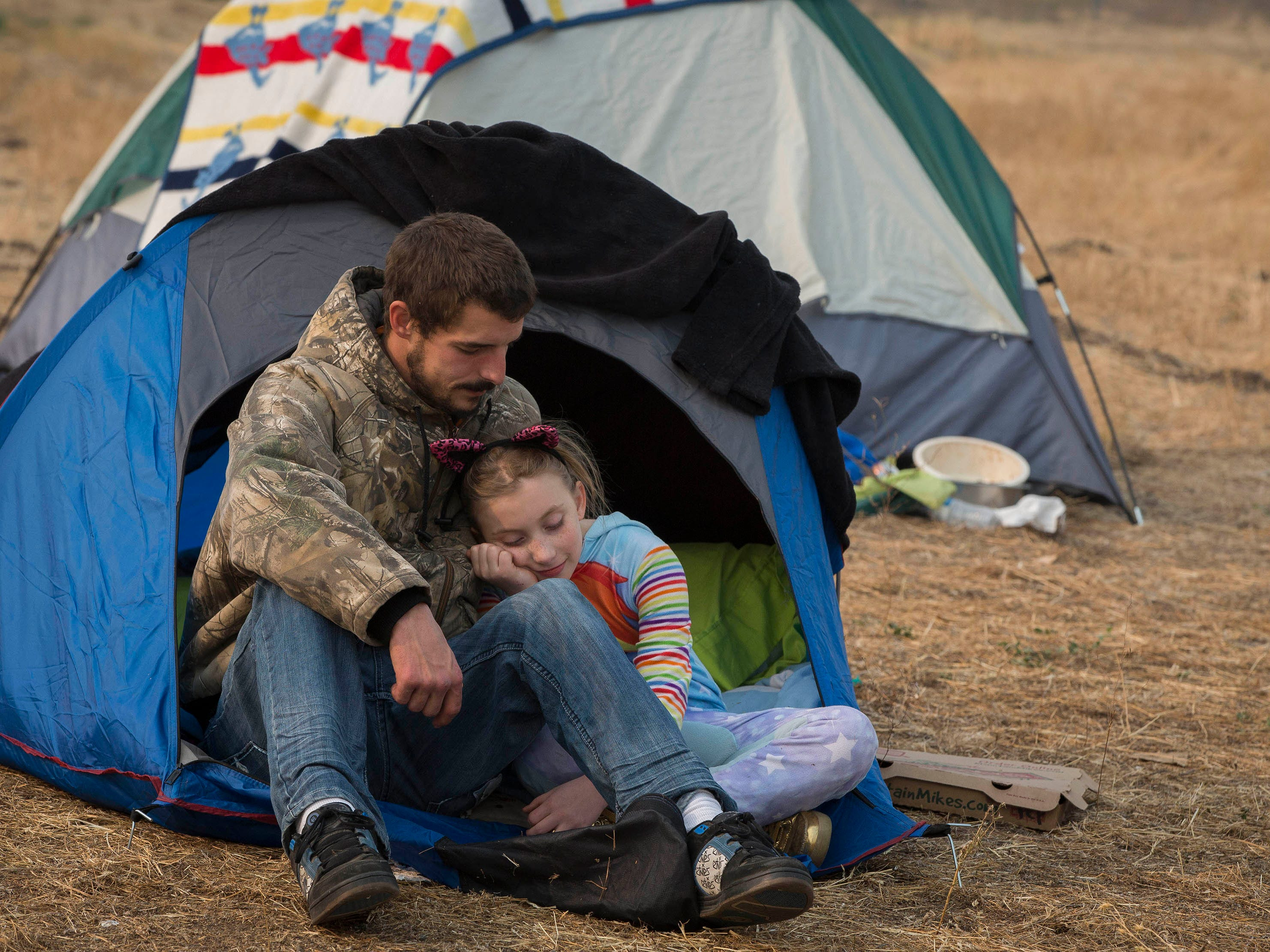 Ryan Belcher, left, comforts his daughter Zoeylee, 10, where they are camping with their family at the Walmart in Chico, Calif. The Belcher family lost their home and vehicles to the Camp Fire.