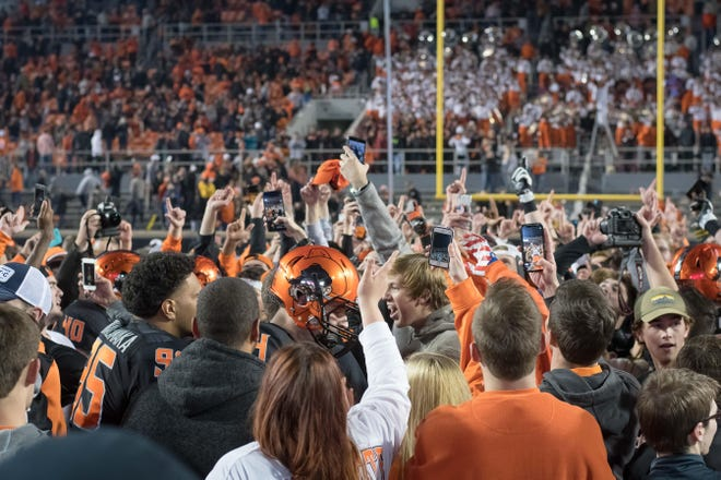 Oklahoma State Cowboys fans rush the field after the team upset the West Virginia Mountaineers at Boone Pickens Stadium.