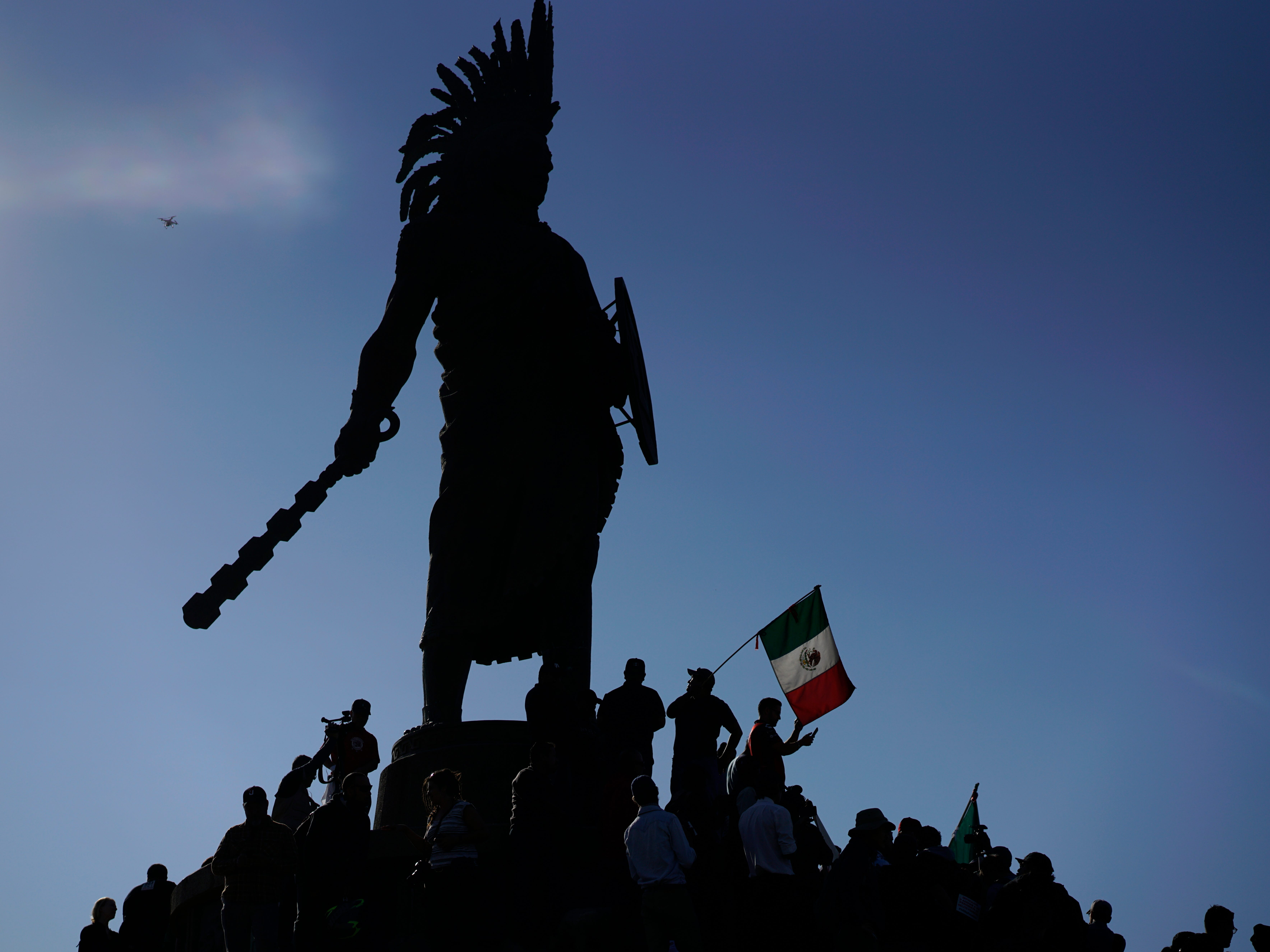 "Demonstrators stand under an indigenous statue of Aztec ruler Cuauhtemoc as they protest the presence of thousands of Central American migrants in Tijuana, Mexico, Sunday, Nov. 18, 2018. Protesters accused the migrants of being messy, ungrateful and a danger to Tijuana; complained about how the caravan forced its way into Mexico, calling it an ""invasion,"" and voiced worries that their taxes might be spent to care for the group as they wait possibly months to apply for U.S. asylum."