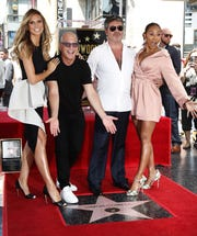 """Simon Cowell (second, right) poses with hosts of """"America's Got Talent"""" Heidi Klum (left), Howie Mandel and Mel B (right) during a ceremony honoring Cowell with a star on the Hollywood Walk of Fame on 22 August 2018."""