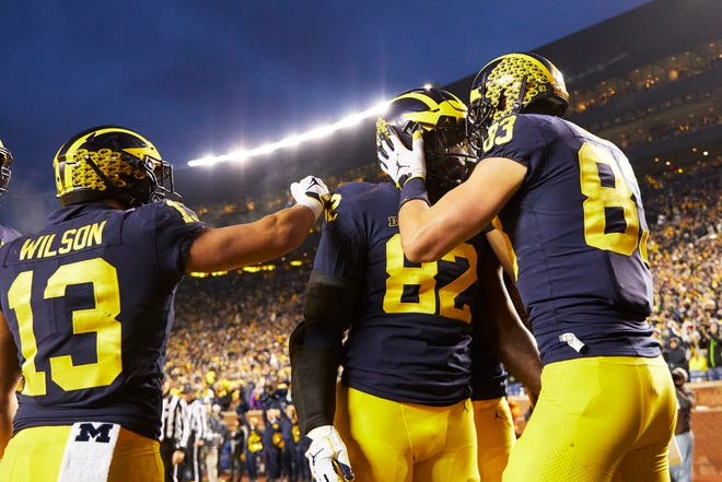 Michigan Wolverines tight end Nick Eubanks (82) receives congratulations from tight end Zach Gentry (83) and running back Tru Wilson (13) after scoring a touchdown in the first half against the Indiana Hoosiers at Michigan Stadium.