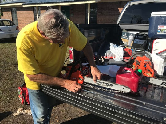 George Edge re-threads the chain of a chainsaw for tree cutting.