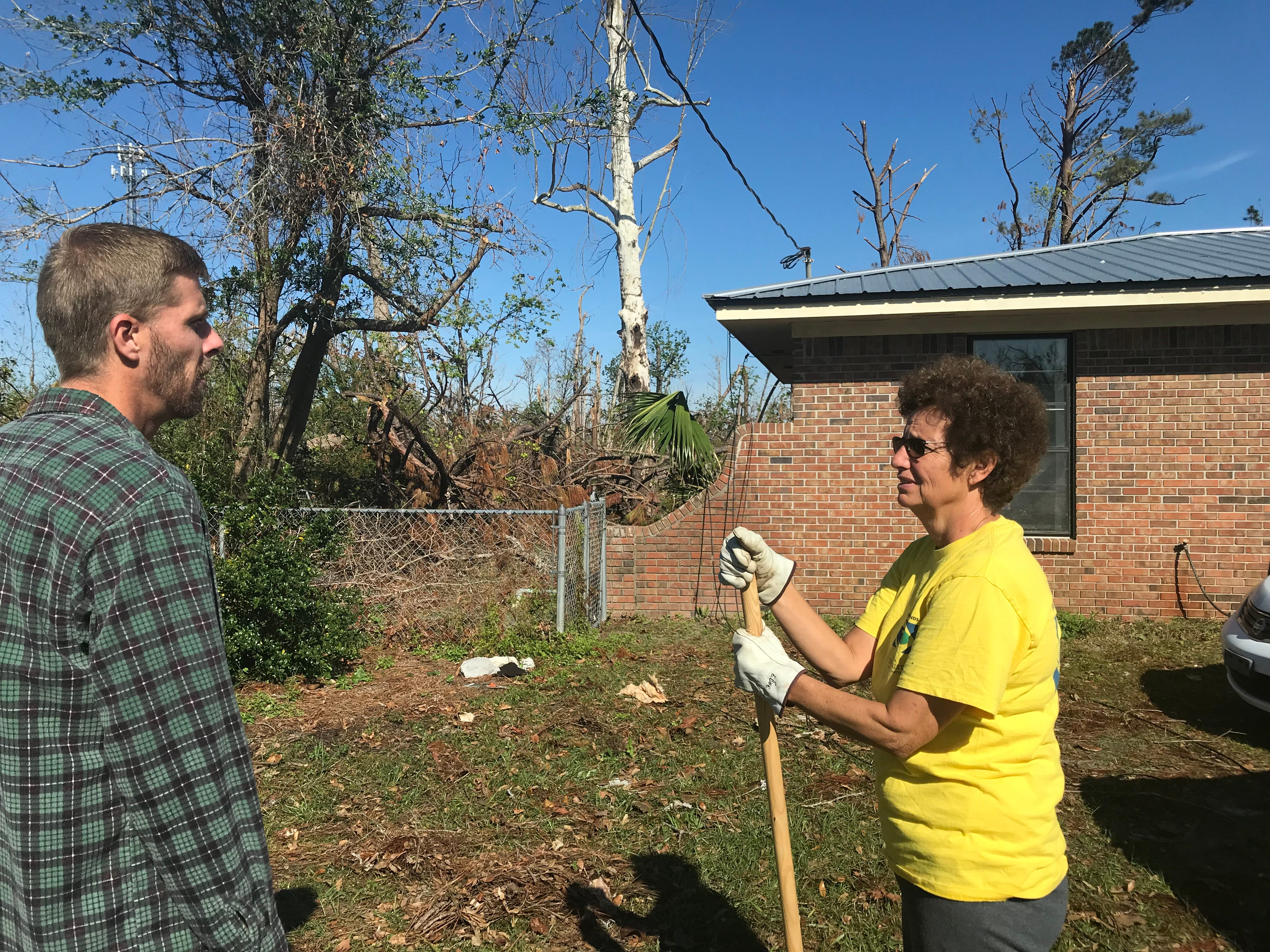 Cathy Edge talks with homeowner Damon Zeigel about the work the volunteers are doing.