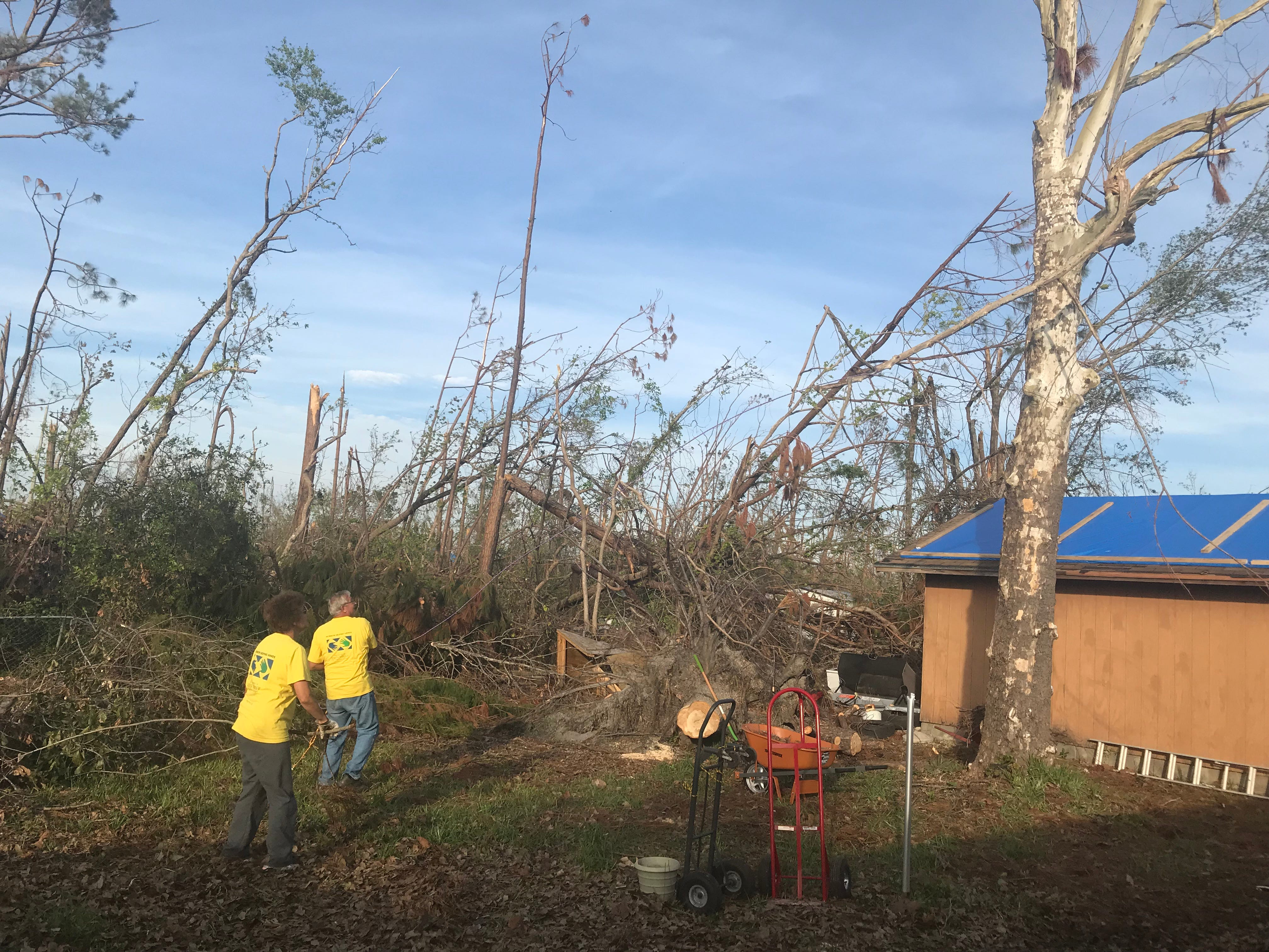 Cathy Edge stands back while her husband, George, attempts to detach a tree limb in Callaway, Florida.
