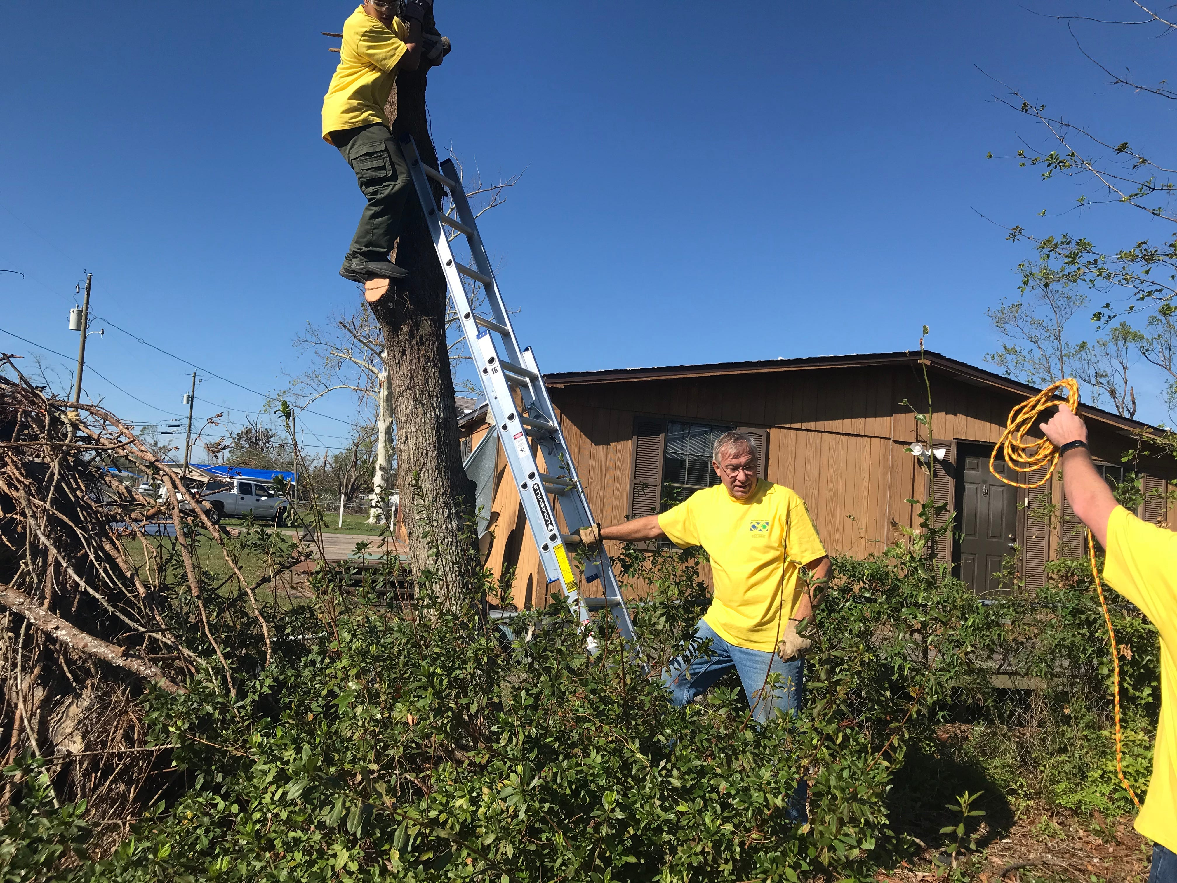 George Edge steadies the ladder as the team works to cut down a tree in Callaway, Florida.