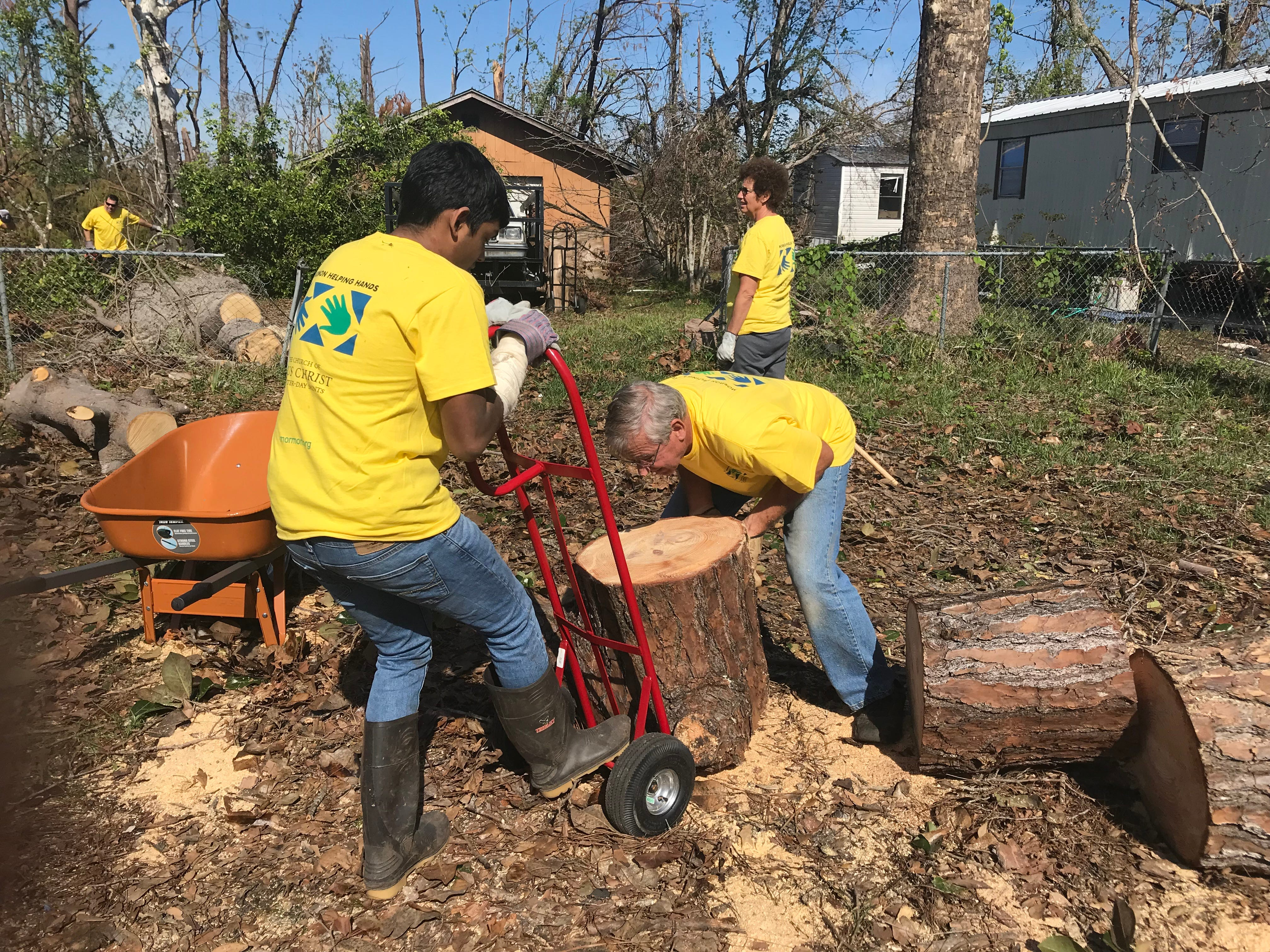 George Edge loads a tree stump onto a dolly to carry out to the debris pile.