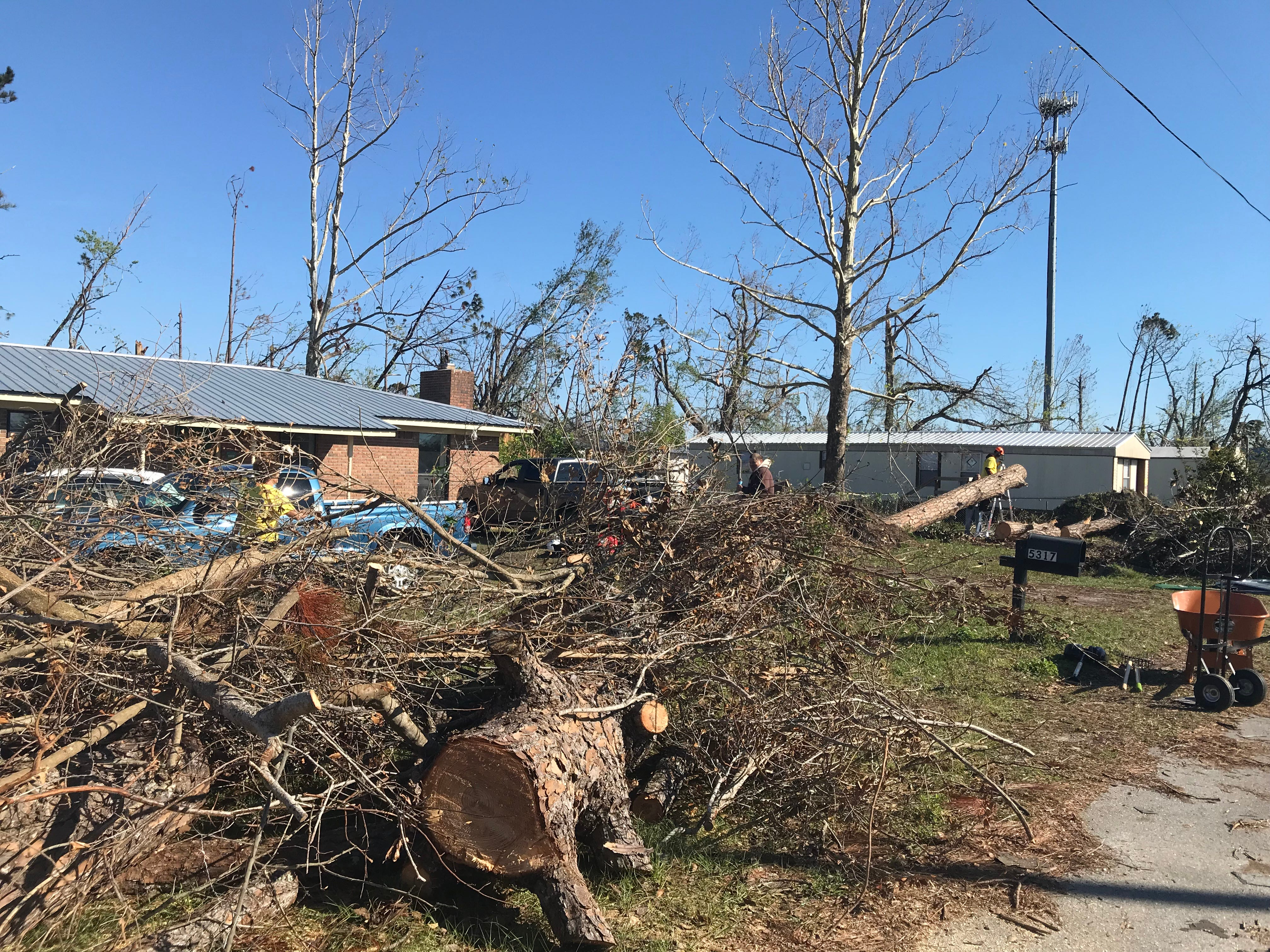 Debris and trees line the front yard of Damon Zeigel's home in Callaway, Florida.