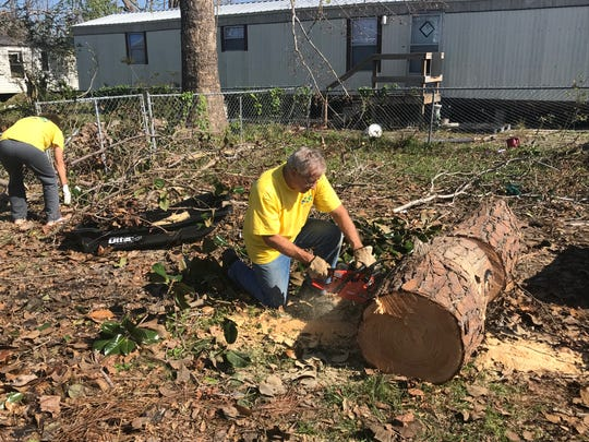 George Edge cuts a large tree into small stumps to carry out to the curb for pickup.
