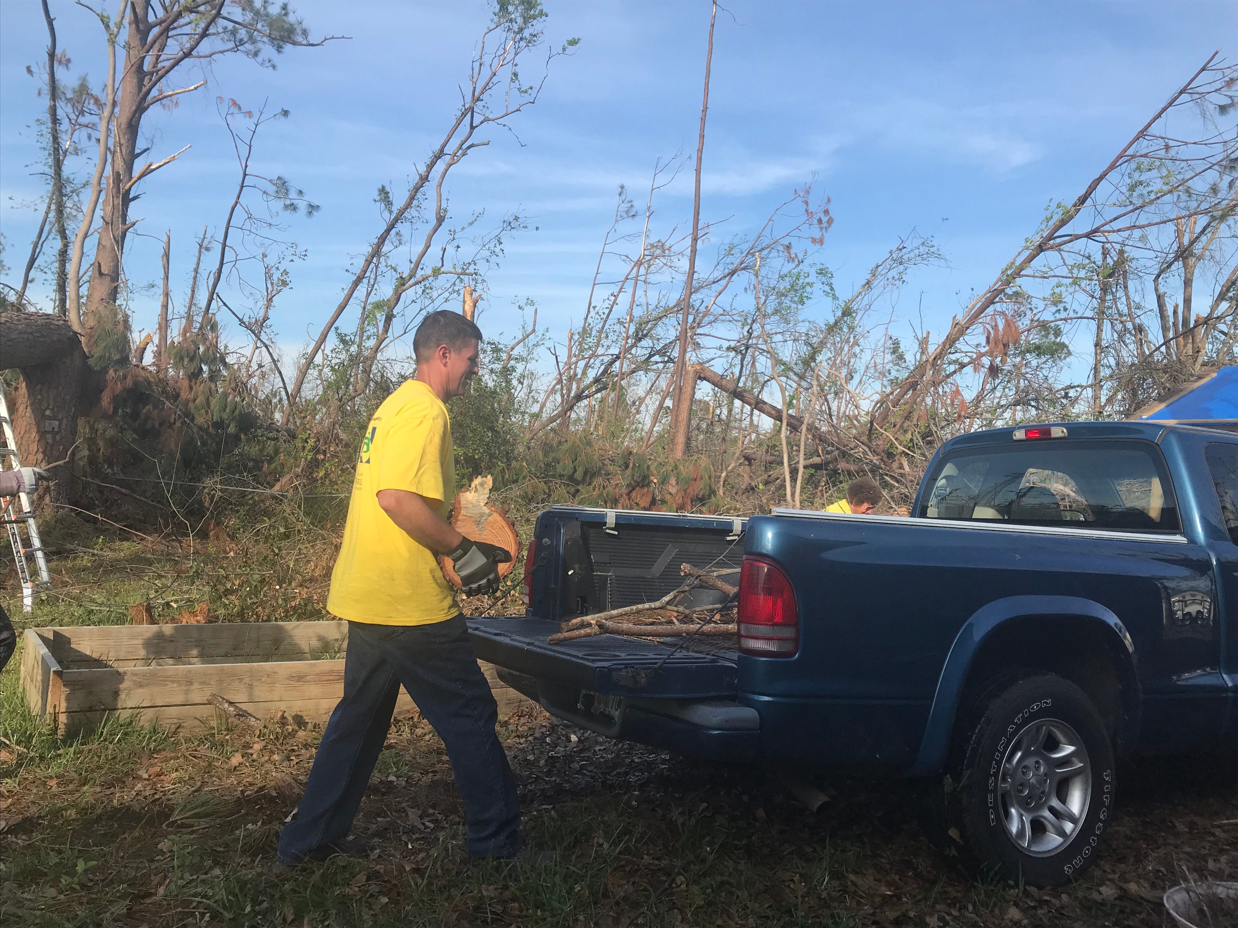 Greenwood's Bishop loads tree stumps into the back of a pick-up truck for faster clean-up.