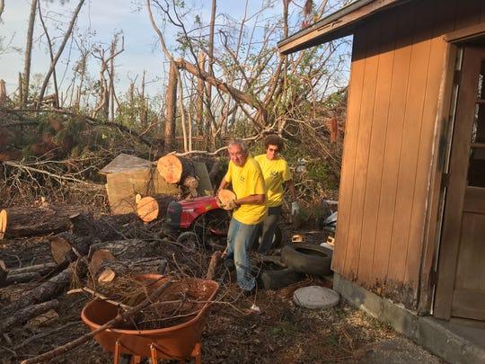 George and Cathy Edge load a tree stump into a wheelbarrow in Callaway, Florida.