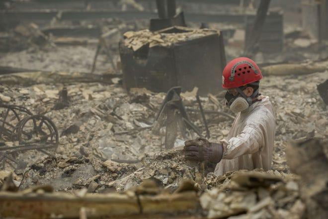 Search and rescue personnel comb through debris searching for remains in Paradise, Calif.